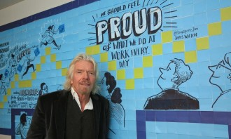 Richard Branson posing for a photo with the post-it wall.