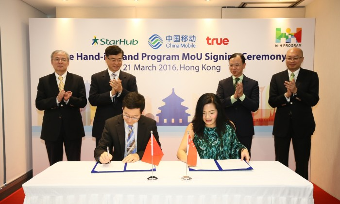 From L to R- Sha Yuejia, Li Yue and Dr Fan Yunjun (seated) of China Mobile with Jeannie Ong (seated), Tan Tong Hai and William Ku of StarHub