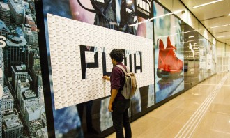 Commuter Peeling Off Coupons from Puma Wallscape