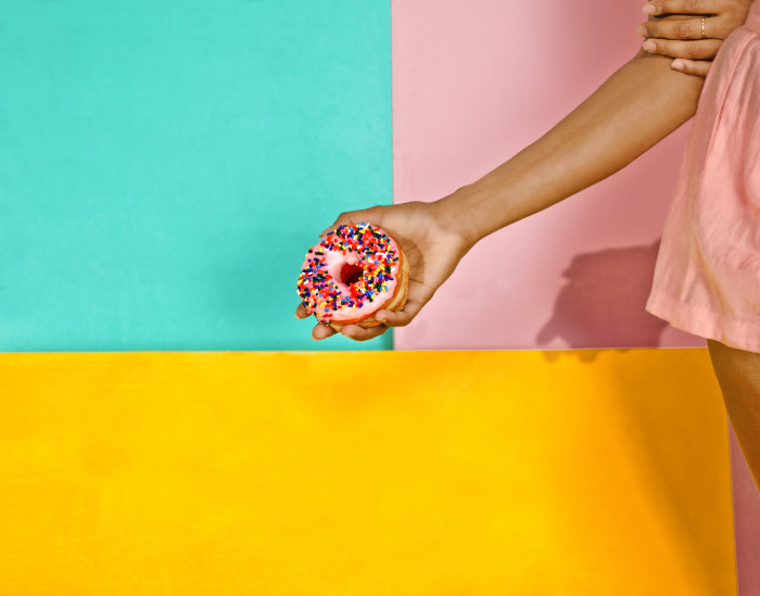 Woman holding donut on colorful backdrop