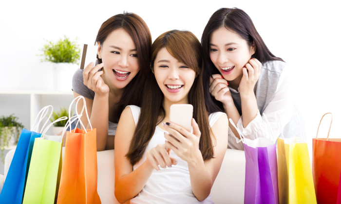47920505 - three young women with shopping bags and looking at smart phone