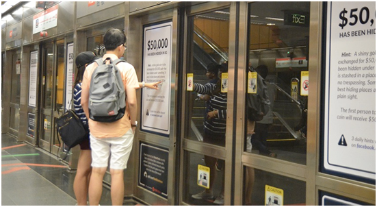 Commuters taking a close look at the transit advertisements found in Newton (NSL) station